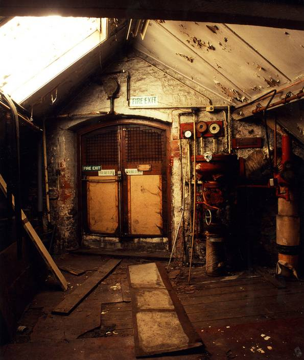 Dimly lit dilapidated interior with machinery