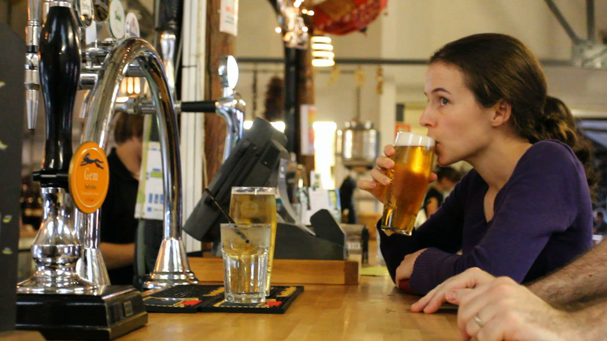 Young woman drinking lager out of a pint glass at the bar in Bocabar